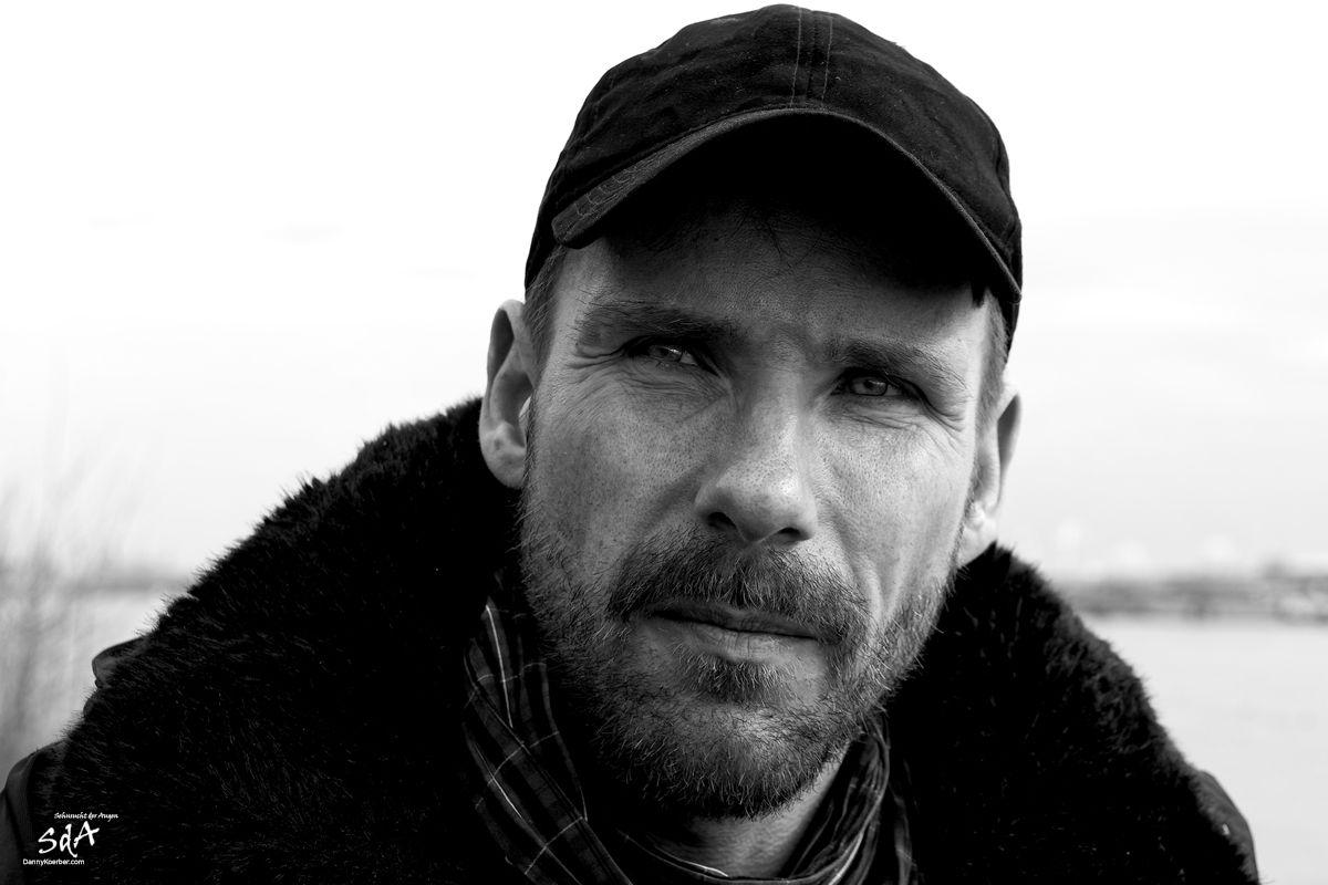 Portrait eines Mannes mit ernster Miene, fotografiert von Danny Koerber für Sehnsucht der Augen.