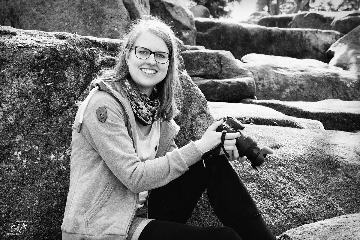 Frauenportrait mit Fotokamera in der Hand, fotografiert in schwarz weiß von Danny Koerber für Sehnsucht der Augen.